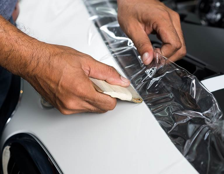 Person peeling off a protective film on a new car.