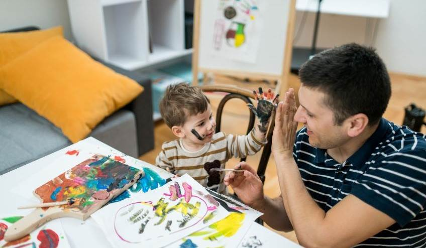 Male and child playing with finger paints
