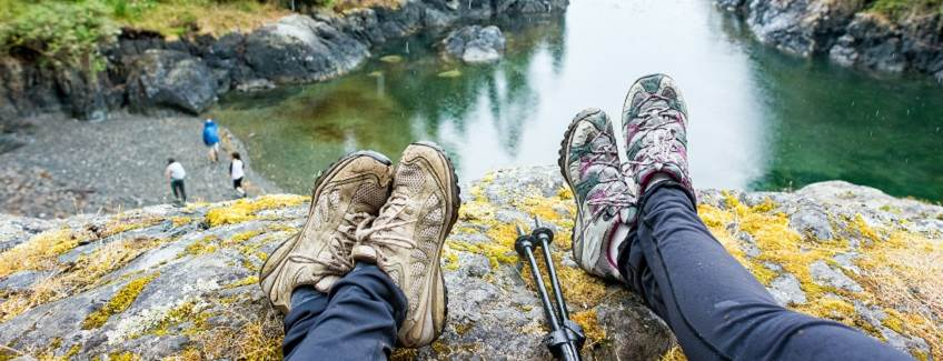 People wearing hiking boots overlooking a lake.