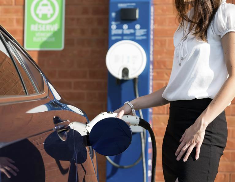 Woman charging an electric vehicle