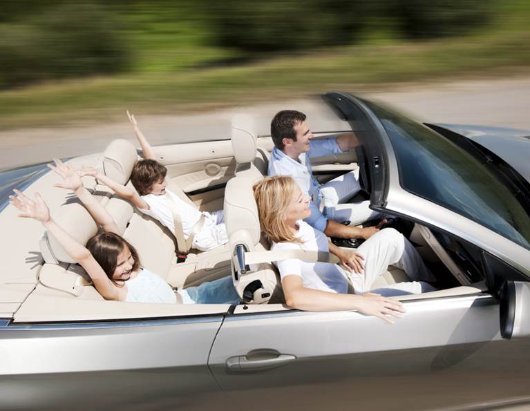 Family driving down the road in a convertible representing adhesives for a powertrain.