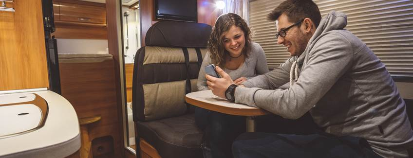 Couple in a camper or RV with wood paneling manufactured with adhesives from H.B. Fuller.