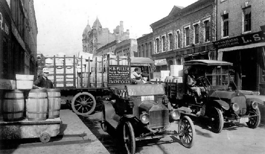 Old H.B. Fuller trucks on a city street.