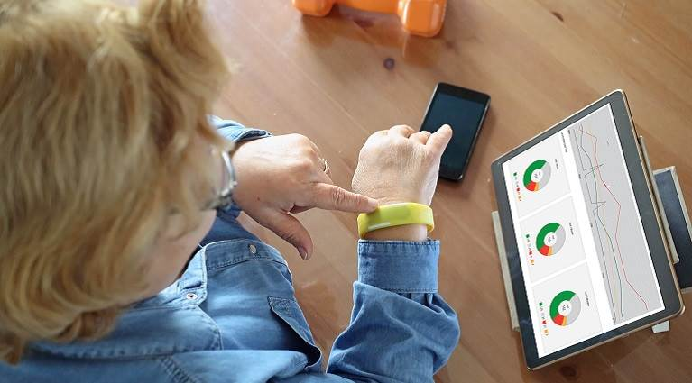 Woman wearing a wearable electronic device in front of a computer.